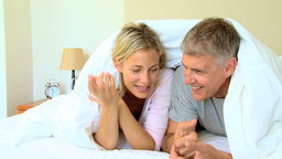 Young couple chatting and laughing under the duvet Footage