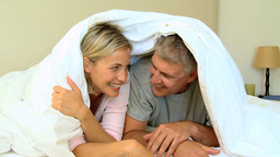 Young couple laughing and posing under the duvet Footage
