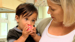 Baby in mothers arms eating a red apple Footage