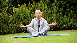 Mature woman doing yoga outdoors on a mat Footage