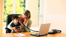 Mother doing office work with baby on her lap Footage