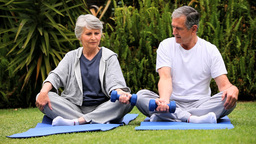 Senior couple doing dumbell exercises on gym mats Footage