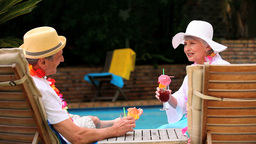 Mature couple drinking cocktails by swimming pool Footage