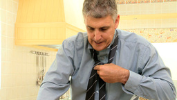 Businessman in kitchen getting dressed quickly Footage