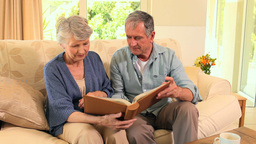 Mature couple looking at an album Live Action