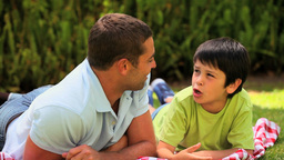 Father and son lying chatting outdoors Footage