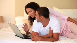 Young couple lying on their bed using a laptop Footage