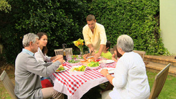 Family with grandparents eating outdoors Footage