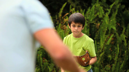 Young boy playing baseball with his father Footage