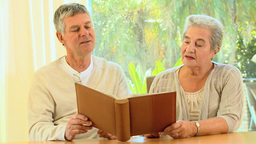 Mature couple reminiscing looking at an album Live Action