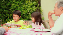 Children eating in the garden with their family Footage