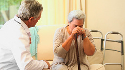 Doctor Visiting A Worried Older Patient stock footage