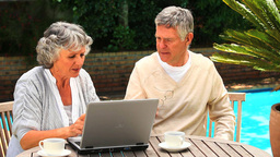 Mature couple sitting outdoors using a laptop Footage