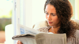 Young woman reading a newspaper Footage