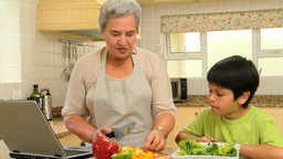 Little boy cooking with his grandmother Footage