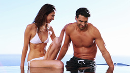 Couple sitting together on the edge of a swimming  Footage