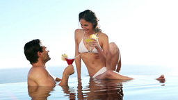 Couple in a swimming pool drinking cocktails Footage