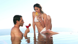Couple holding cocktail glasses in a swimming pool Footage