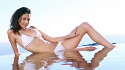 Young woman sunbathing beside a swimming pool Footage