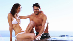 Smiling couple sitting in a swimming pool Footage