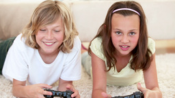 Brother and sister lying while playing video games Footage