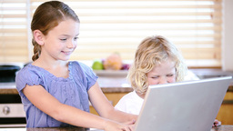 Young girl using a laptop with her brother Footage