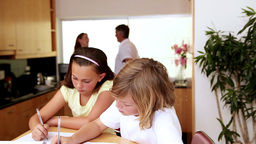 Siblings doing their homework in the kitchen with their parents behind them Footage