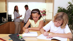 Brother and sister doing homework in the kitchen with parents behind them Live Action