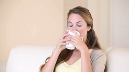 A woman sitting while drinking coffee Footage