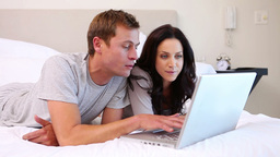 Couple using laptop on their bed Footage