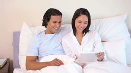 Couple sitting on their bed with tablet computer Footage