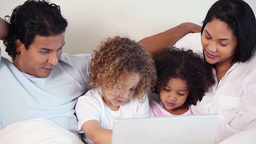 Family with laptop on their bed Footage