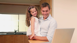Father and daughter with laptop in the kitchen Live Action