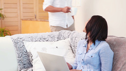 Woman using laptop in the living room as her boyfriend walks in Live Action