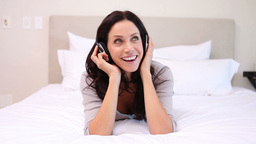 Woman on her bed moves to the music she is listeni Footage