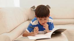 Boy writing in a magazine Footage