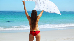 Brunette holding her sarong Live Action