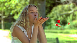 Blonde woman blowing in slow motion on petals Footage