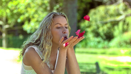 Blonde woman in slow motion blowing on petals Footage