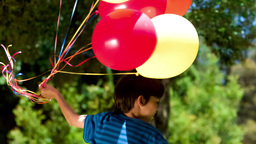 Boy holding balloons in slow motion Footage
