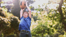 Child playing in slow motion with a rugby ball Footage
