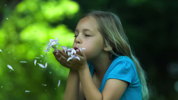 Girl in slow motion blowing petals Footage