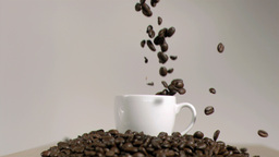 Coffee beans dropping in cup in super slow motion Footage
