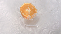 Orange falling into water in super slow motion Footage