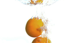 Grapefruits dropped into water in super slow motio Footage