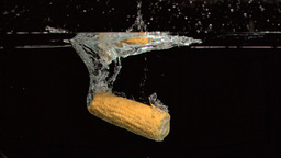 Corn cob dropped into water in super slow motion Footage