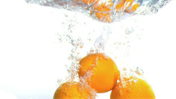 Grapefruits falling into water in super slow motio Footage