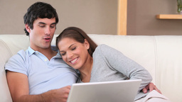 Smiling couple using a laptop Footage