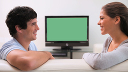 Couple talking in front of the television Footage