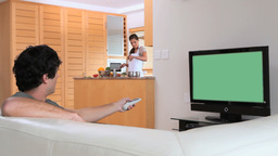 Man watching the television while his wife is prep Footage